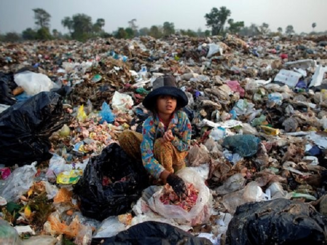 Child resting at landfill