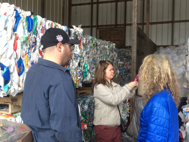 3 people looking at bales of plastic recycling