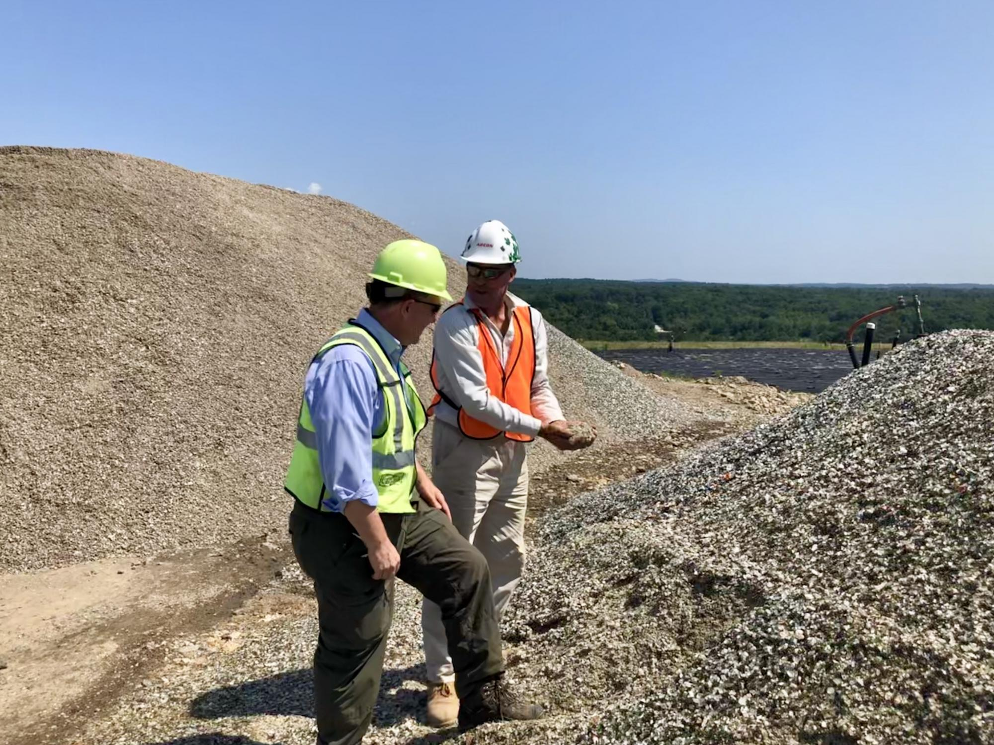 Bob Magnusson of Waste Management (left) and Ivar Martin, NRRA's glass-crushing vendor, inspect PGA material at a Waste Management facility in Rochester, N.H. that serves as one of NRRA's PGA host sites.